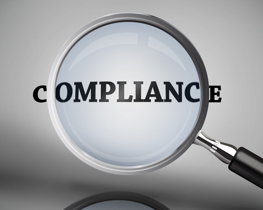 Magnifying glass showing compliance word on grey background.jpeg
